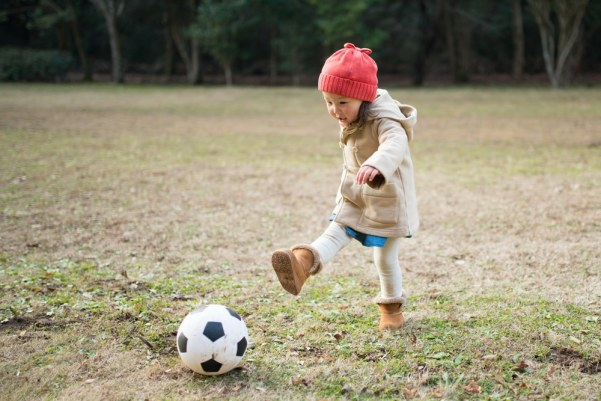 Little girl playing football on frosty grass