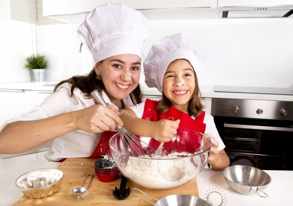 Mother and daughter making pancakes together