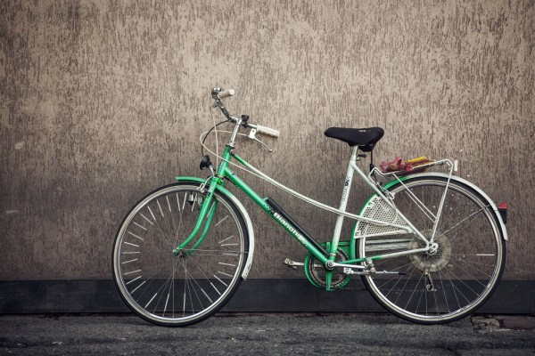 Green bicycle leaning against a wall