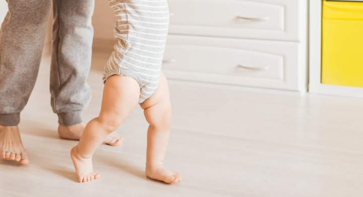 Baby taking steps assisted by a parent