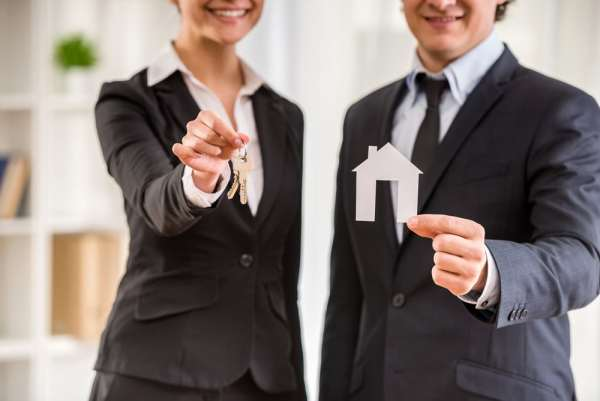 Business people holding model house and keys