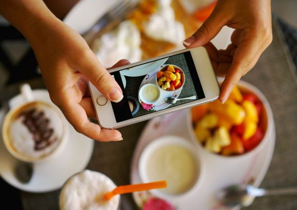 Woman photographing food on smart phone