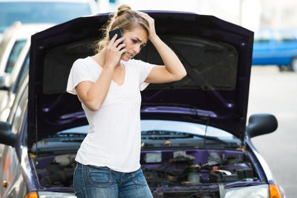 Distressed woman calling for help in front of broken down car
