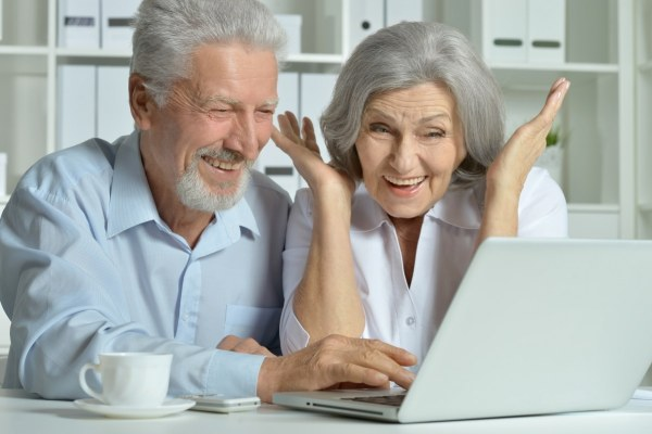 Senior couple using a laptop looking excited