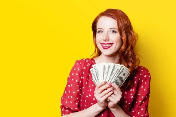 Smiling woman holding cash