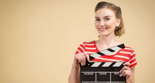 Young woman holing clapper board