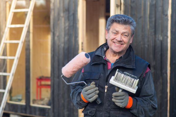 Happy man holding decorating tools