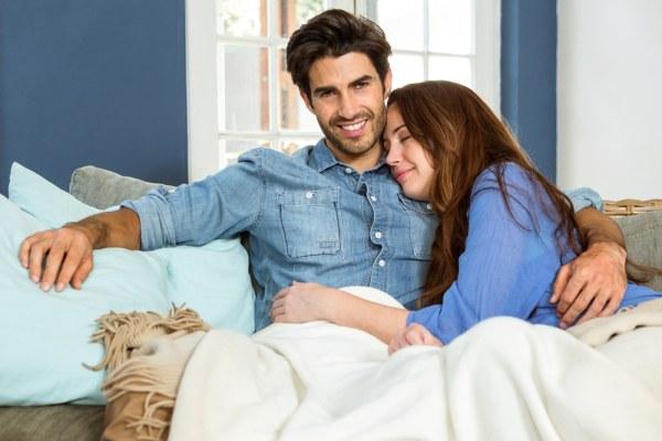 Happy man cuddling woman on sofa