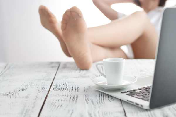 Woman in tights with feet up on her desk