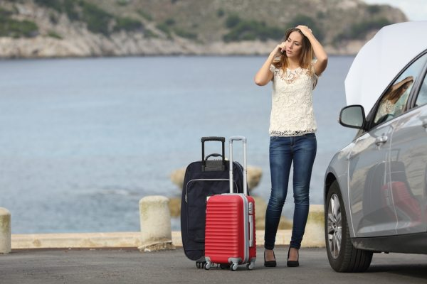 Stressed unhappy worman with hire car and suitcases