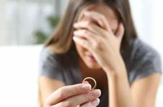 Unhappy woman holding wedding ring