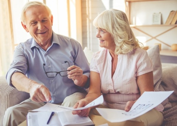 Happy older couple looking at documents