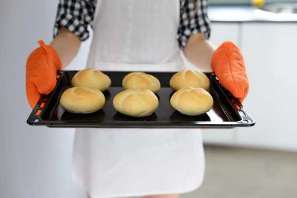 Student holding hot tray with oven gloves
