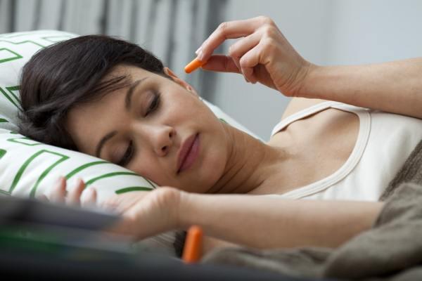 Woman using ear plugs