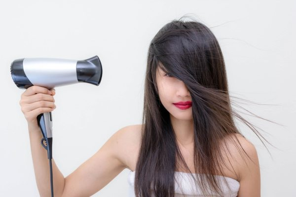 Young woman using hair dryer