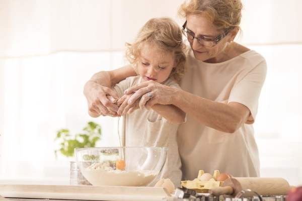 Senior woman baking with little girl