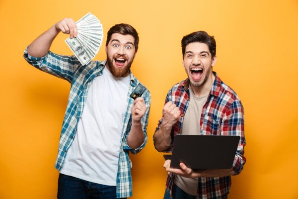 Excited young men holding a laptop and money
