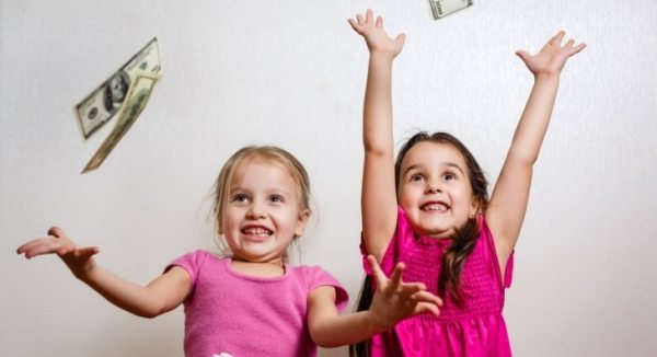 Excited little girls catching raining money