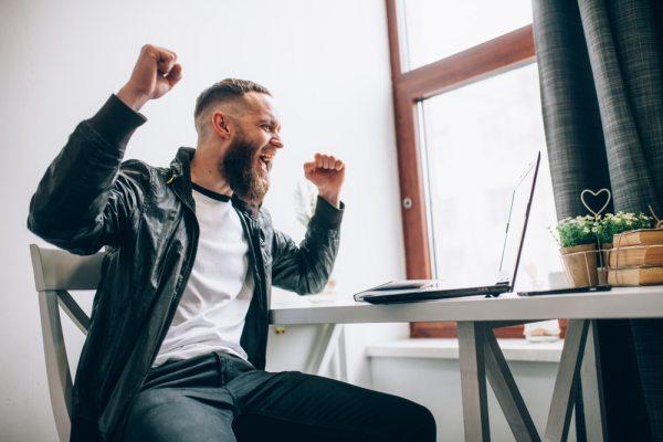 Happy man betting at laptop
