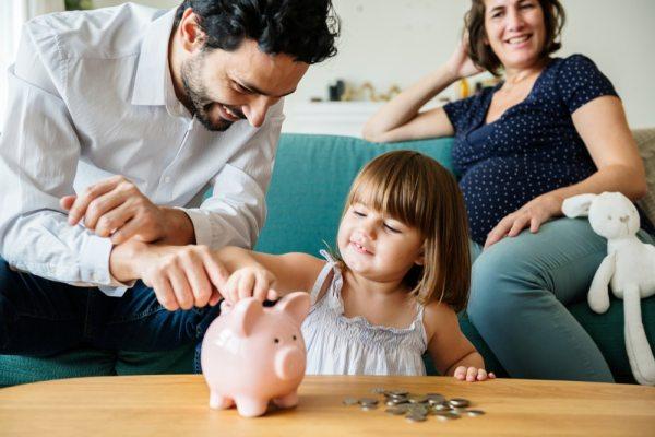 Parents watching little girl put coins in piggy bank