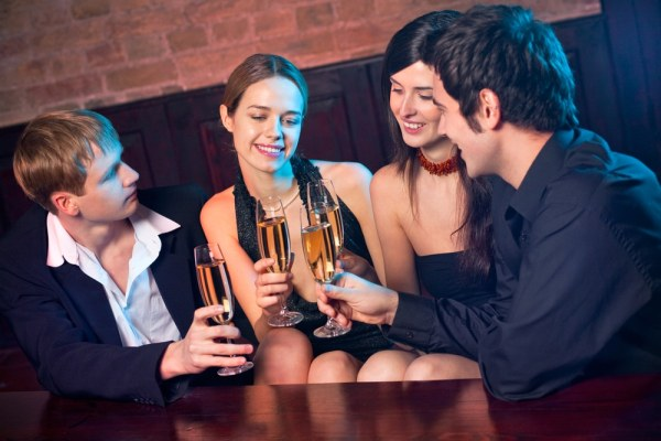 two couples having drinks in a bar