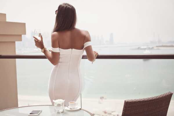 Wealthy woman drinking champagne on a balcony