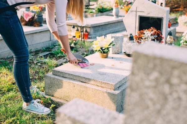 Woman cleaning gravestone