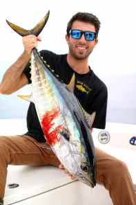 The author holding a yellowfin tuna on a boat
