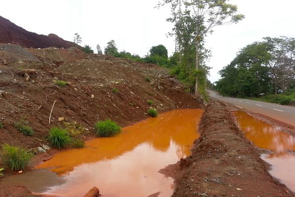Salah satu izin tambang nikel di Kecamatan Bahodopi, tetapt di tepi jalan raya. Air galian tambang pun meluber membasahi jalanan. Tak jauh dari jalan, lubang-lubang tambang menganga. Tanpa pembatas. Kini, ditinggalkan begitu saja tanpa reklamasi.  Foto: Sapariah Saturi