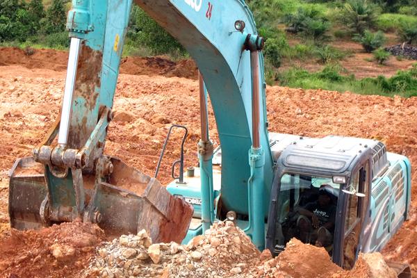 Sebuah eksavator tampak sedang bekerja mengeruk tanah di Desa Mekar Utama untuk kepentingan pembangunan smelter PT. HPAM dan PT. WHW Alumina Refinery. Foto: Andi Fachrizal