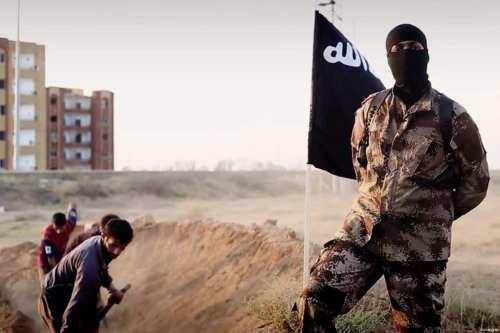 Un combatiente del ISIS frente a un grupo de prisioneros que cavan sus propias tumbas.