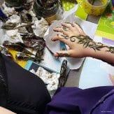 MANAMA, BAHRÉIN. Estudiadno diseños de tatuajes de henna.