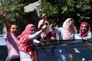 GAZA CITY, PALESTINA: Un grupo de estudiantes palestinas celebran los resultados de sus exámenes tras ser informadas de ello en el final del curso escolar por las calles de la ciudad de Gaza