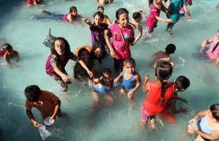 GAZA, PALESTINA: Niños palestinos chapotean en el agua en un parque de atracciones en el tercer día de la Fiesta del Sacrificio.
