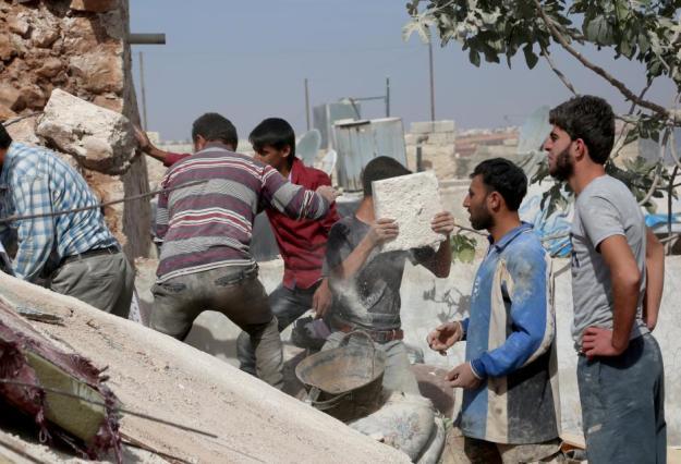 Alepo, Siria, 17 de Octubre. Los supervivientes a los ataques buscan víctimas entre los escombros. ( Ahmed al Ahmed, Agencia Anadolu).