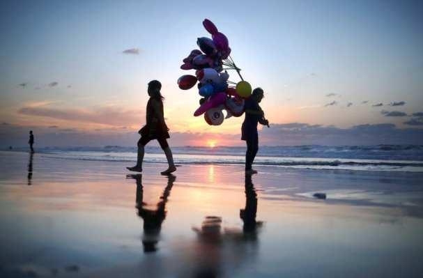 CIUDAD DE GAZA, GAZA - 17 de noviembre: Un vendedor ambulante camina en la orilla de la playa de Gaza para vender globos el 17 de noviembre de 2016 en la ciudad de Gaza, Gaza. (Ali Jadallah - Agencia Anadolu)