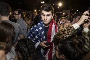 WASHINGTON: Un hombre exhibe una bandera estadounidense entre la multitud de partidarios de Trump y Clinton concentrados frente a la Casa Blanca en espera de los resultados electorales. (Samuel Corum/Agencia Anadolu)