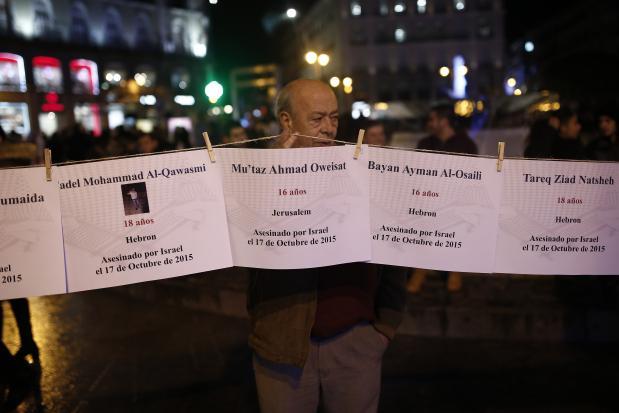 MADRID, ESPAÑA - 29 DE NOVIEMBRE: Un hombre muestra fotografías de palestinos asesinados por Israel, mientras los manifestantes se reúnen para organizar una cadena humana de protesta en apoyo de los palestinos durante el Día Internacional de Solidaridad con el Pueblo Palestino en la Puerta del Sol, Madrid, España, el 29 de noviembre de 2016. (Burak Akbulut - Agencia Anadolu)