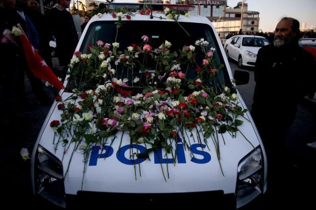 Un vehículo de la policía con flores, como la gente se reúne por las víctimas de los ataques terroristas de Estambul cerca de la Arena Vodafone en Estambul Besiktas, Turquía el 11 de diciembre de 2016 [Onur Çoban / Agencia Anadolu]