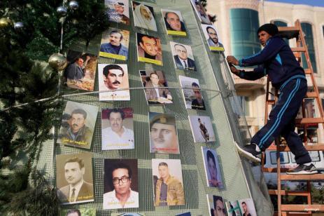 AL-ZARIA, CISJORDANIA- Un joven palestino decora un árbol con fotos de mártires palestinos