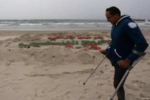 CIUDAD DE GAZA, GAZA- El artista palestino Mohammed Totah, con una pierna amputada, posa para una foto detrás de una escultura de arena para conmemorar el día de los heridos palestinos