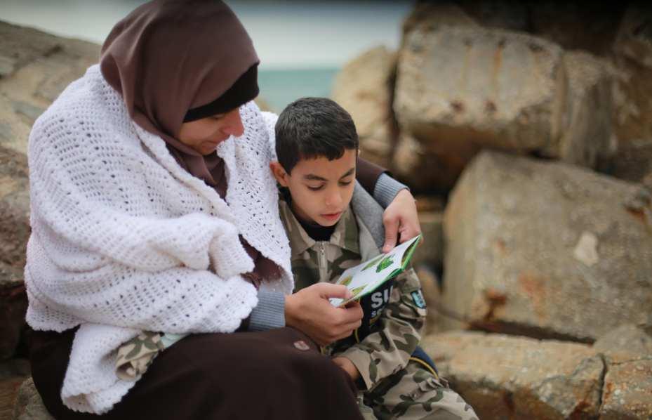 Familias y jóvenes participan en la iniciativa de la Cadena de Lectores de Palestina, en Gaza, Palestina, el 19 de Marzo de 2017. (Fotografía: Mohammed Assad)