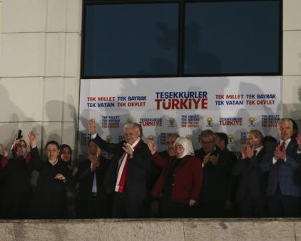 """ANKARA, TURQUÍA - 16 DE ABRIL: El primer ministro turco y el líder del Partido de la Justicia y el Desarrollo de Turquía (AKP), Binali Yildirim (C), su esposa Semiha Yildirim (CD) saludan a las masas desde el balcón de la sede del AKP. Los resultados preliminares oficiosos del referéndum constitucional de Turquía muestran la ventaja de los votos del """"sí"""" freente a los del """"no"""". En Ankara, Turquía el 16 de Abril de 2017. El pueblo turco votó el cambio propuesto a un sistema presidencial para reemplazar a la democracia parlamentaria, con 18 artículos propuestos para ser enmendados en la constitución. (Abdülhamid Hoşbaş - Agencia Anadolu)"""