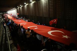 Los manifestantes portaban una bandera turca de 2016 metros como parte de los actos convocados para celebrar el día de la Democracia y la Unidad Nacional, que conmemora el fracaso del golpe de Estado el 15 de julio de 2017 La gente llega desde distintos puntos al Puente de los Mártires para la manifestación que conmemora el día de la Democracia y la Unidad Nacional el 15 de Julio de 2016 ([Stringer / Anadolu Agency]