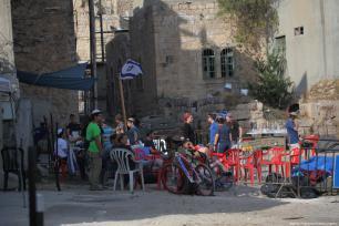 Los colonos se reúnen fuera de un hogar palestino después de echar a sus dueños legales, el 26 de julio de 2017 en la ciudad ocupada de Hebrón, Cisjordania. [Mamoun Wazwaz / Anadolu Agency]