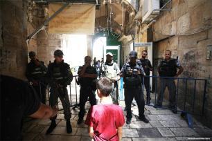 Un niño palestino de pie ante los soldados israelíes que custodian una de las entradas al complejo de la mezquita de Al-Aqsa. E Jerusalén, el 18 de julio de 2017 (Mostafa Alkharouf/Agencia Anadolu)