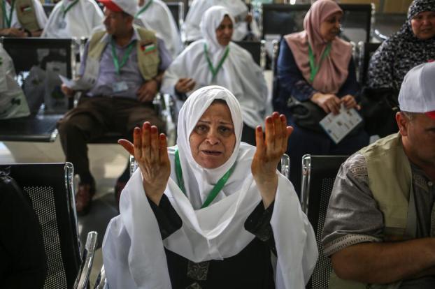 Mujeres y hombres palestinos esperan cruzar el cruce de Rafah de camino a la ciudad más sagrada del Islam, La Meca en Arabia Saudí para realizar una peregrinación, Gaza el 14 de agosto de 2017 [Ali Jadallah / Agencia Anadolu]