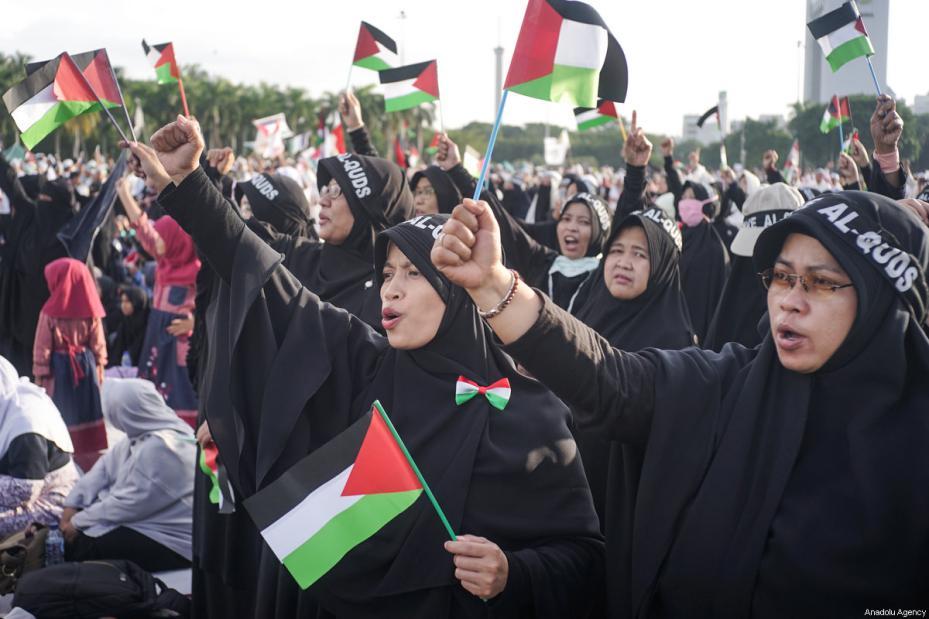 Mujeres manifestantes visten pañuelos en los que se ve inscrito Al-Quds y agitan banderas palestinas en la manifestación para apoyar a Palestina en el Monumento Nacional en Yakarta, Indonesia, 17 de diciembre de 2017 [Agencia Nani Afrida / Anadolu]