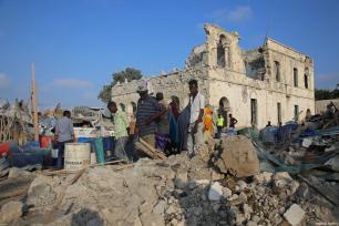Un grupo de personas inspecciona el lugar tras los ataques perpetrados cerca del edificio de la Agencia Nacional de Inteligencia y Seguridad de Somalia (NISA) en Mogadiscio, Somalia, 24 de febrero de 2018 [Agencia Sadak Mohamed / Anadolu]