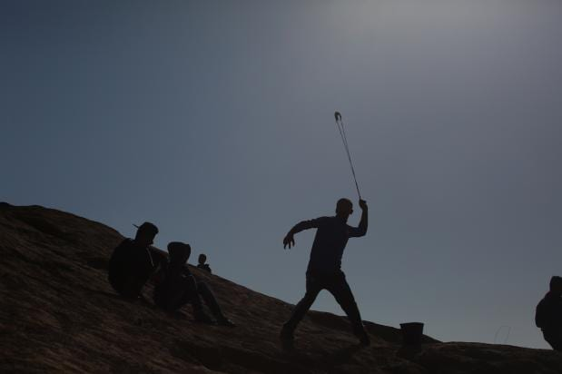 """Un joven tira piedras contra las fuerzas de seguridad israelíes que usan gas lacrimógeno y munición real contra los palestinos concentrados con motivo de la """"Marcha del Retorno"""", en la que exigen su derecho al retorno y la eliminación del bloqueo israelí, Gaza, 1 de abril, 2018 (Hassan Jedi - Agencia Anadolu)"""